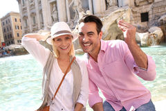 Couple throwing coins in Trevi Fountain to be lucky Stock Image