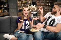 Couple throwing popcorn while watching movie at home Royalty Free Stock Photography