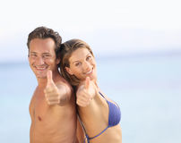 Couple with thumbs up enjoying their holidays Stock Photos
