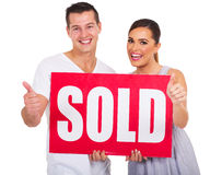 Couple thumbs up. Happy couple holding sold sign and giving thumbs up Royalty Free Stock Photos