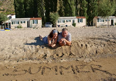 Couple thumbs up at sand beach. Couple thumbs up at sandy beach on summer holidays Stock Images