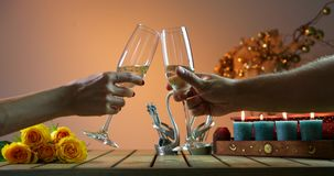 Couple tinkles glasses. Two glasses of champagne, candles on the wooden table. Cheers. Romantic evening. Bottle of champagne with two glasses. Woman pours stock video footage