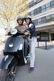 Couple about to ride scooter Royalty Free Stock Image