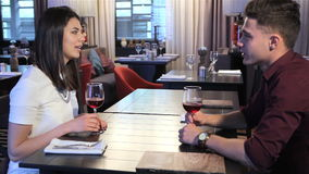 Couple toast at the restaurant at the restaurant. Young caucasian couple toasting at the restaurant. Side view of attractive people having romantic date at the stock video footage