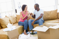 Couple toasting champagne by boxes in new home. Smiling Royalty Free Stock Photo