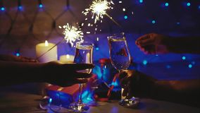 Couple toasting with champagne christmas scene and sparkler. Bokeh blinking background slow motion close up stock video