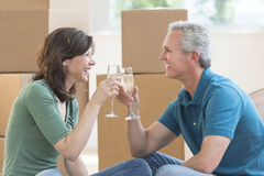 Couple Toasting Champagne Flutes In New House. Happy mature couple toasting champagne flutes against cardboard boxes in new house Stock Photos