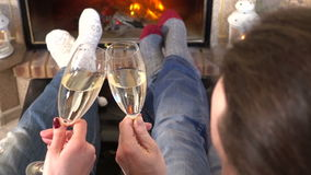 Couple toasting of champagne heating feet together near fireplace
