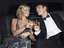 Couple Toasting Champagne In Limousine. Happy young glamorous couple toasting champagne in limousine Stock Image