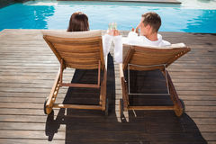Couple toasting champagne by swimming pool Royalty Free Stock Photos