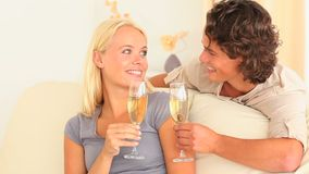 Couple toasting with Champagne. In their livingroom stock footage