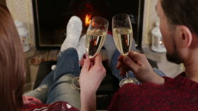 Couple toasting of champagne together near fireplace stock video footage