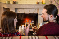 Couple toasting of champagne together near fireplace Stock Image