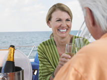 Couple Toasting Champagne On Yacht. Cheerful middle aged women with men toasting champagne on yacht Stock Images