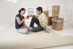 Couple Toasting Coffee Cups In New Home Stock Photography