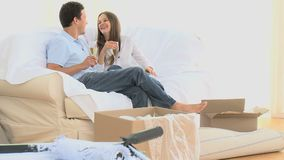 Couple toasting with a glass of white wine during the move. Couple toasting with a glass of white wine while sitting on the sofa during the move stock footage