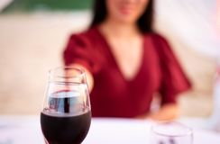 Couple toasting with glass of wine a date. Closeup, woman, clinking, wineglass, romantic, celebration, drink, romance, rural, dinner, happy, white, hand royalty free stock images