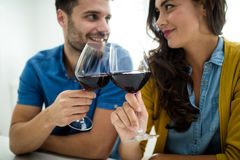 Couple toasting glasses of red wine in the kitchen Royalty Free Stock Photography