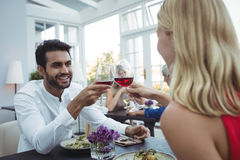 Couple toasting glasses of wine while having meal Royalty Free Stock Images