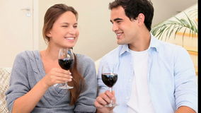 Couple toasting with glasses of wine. In the living room stock video footage