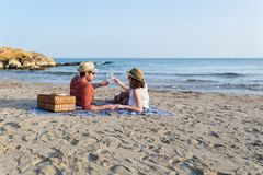 Couple toasting while holding hands on a mediterranean beach at sunset stock image