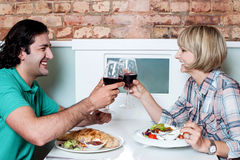 Couple toasting over a restaurant table Stock Photo