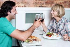 Couple toasting over a restaurant table Royalty Free Stock Photography