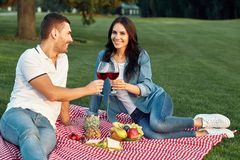 Couple toasting with red wine glasses stock photo