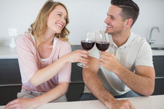 Couple toasting red wine glasses at table Royalty Free Stock Photos