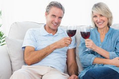 Couple toasting with red wine on the sofa looking at camera Royalty Free Stock Photo