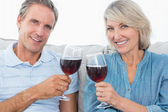Couple toasting with red wine on the sofa smiling at camera Stock Photo