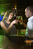 Couple toasting their beer glasses at bar counter Stock Photos