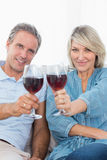 Couple toasting to the camera with red wine on the couch Stock Image