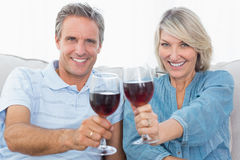 Couple toasting to the camera with red wine on the sofa Stock Photography