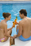 Couple toasting tropical drinks at poolside Stock Images