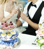 Couple toasting at wedding. With cakes on table Stock Photos