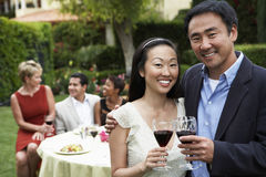 Couple Toasting Wine With Friends In Background. Portrait of happy Asian couple toasting wine with friends in background Royalty Free Stock Photography