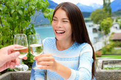 Couple toasting wine glass at outdoor restaurant. Asian woman cheering with alcohol drink in Swiss Alps, Switzerland in summer at outside terrace near lake Royalty Free Stock Photo