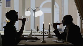 Couple Toasting Wine Glass in Restaurant. Man and woman on romantic dinner drinking at restaurant, celebrating valentine day. Silhouette of man and woman stock footage