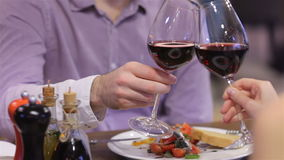 Couple toasting wine glasses. Celebrating a Valentine's Day at a restaurant. Young couple sitting in a cafe drinking coffee and tea. Enamored a gala dinner for stock footage
