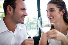 Couple toasting wine glasses at dining table Stock Image