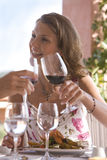 Couple toasting wine glasses at patio table.  royalty free stock photos