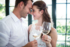 Couple toasting wine glasses in a restaurant. Couple looking face to face and toasting wine glasses in a restaurant Royalty Free Stock Photos