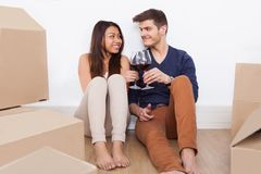 Couple toasting wineglasses in new home Stock Photo