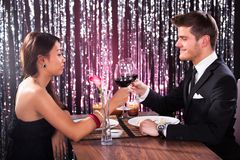Couple toasting wineglasses at restaurant table Royalty Free Stock Photos