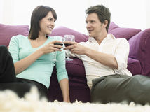 Couple Toasting Wineglasses By Sofa Royalty Free Stock Photography