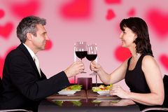 Couple toasting wineglasses at table in restaurant Stock Photo