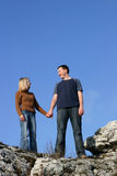 Couple - Together. Young man and woman standing on a rock and smiling. Blue sky as a background Stock Photography
