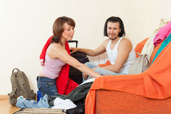 Couple together choosing clothes for vacation Stock Photos