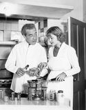Couple together in the kitchen preparing a fondue Royalty Free Stock Photos